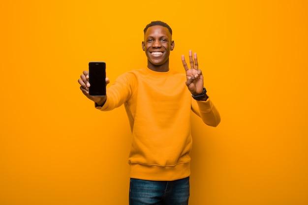 Jeune homme noir afro-américain contre le mur orange avec un téléphone intelligent
