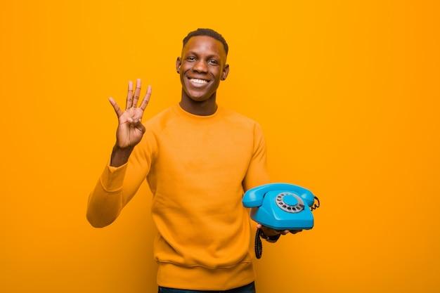 Jeune homme noir afro-américain contre le mur orange avec un téléphone vintage