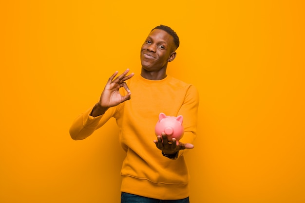 Jeune homme noir afro-américain contre le mur orange avec une tirelire