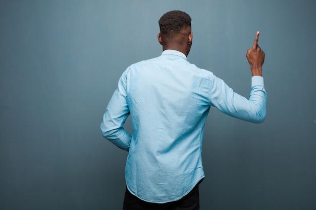 Jeune homme noir afro-américain debout et pointant vers l'objet sur l'espace de copie, vue arrière contre le mur de grunge