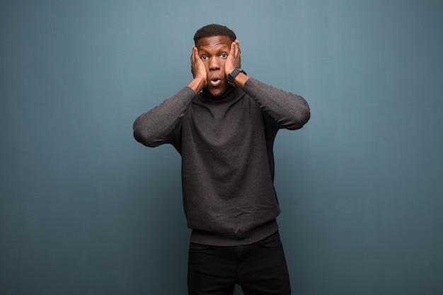 Jeune homme noir afro-américain à la désagréablement choqué, effrayé ou inquiet, la bouche grande ouverte et couvrant les deux oreilles avec les mains contre le mur de grunge