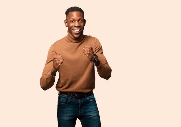 Jeune homme noir afro-américain se sentant choqué, excité et heureux, riant et célébrant le succès, disant wow! contre le mur beige