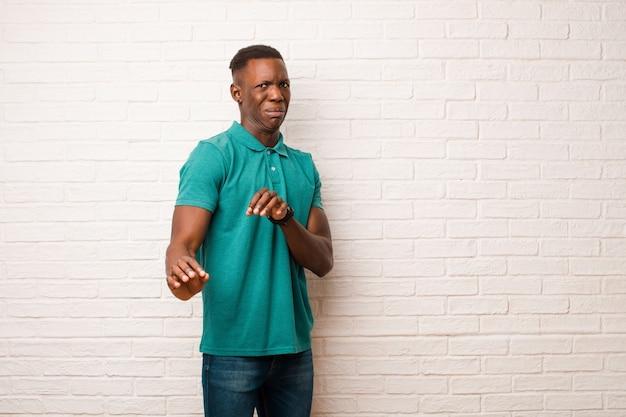 Jeune homme noir afro-américain se sentant dégoûté et nauséeux, reculant devant quelque chose de méchant, puant ou puant, disant beurk contre le mur de briques
