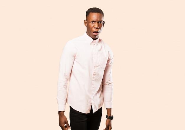 Jeune homme noir afro-américain se sentant terrifié et choqué, avec la bouche grande ouverte en surprise contre le mur beige