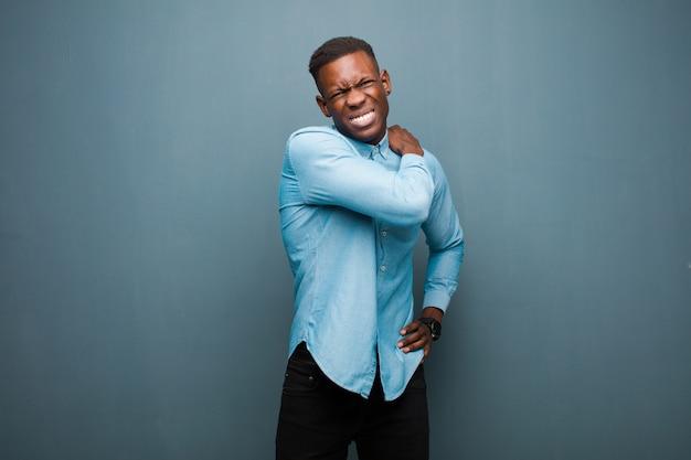 Jeune homme noir afro-américain se sentir fatigué, stressé, anxieux, frustré et déprimé, souffrant de douleurs au dos ou au cou
