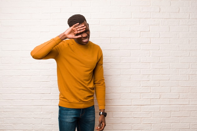 Jeune homme noir afro-américain à stressé, fatigué et frustré, séchant la sueur du front, se sentant désespéré et épuisé sur le mur de briques