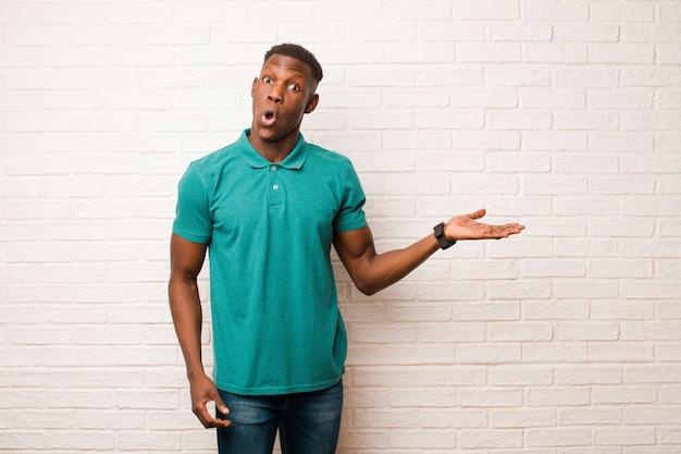 Jeune homme noir afro-américain à la surprise et choqué, avec la mâchoire tombée tenant un objet avec une main ouverte sur le côté sur le mur de briques