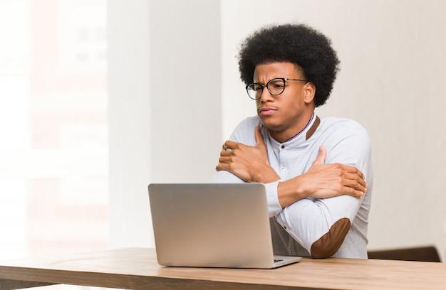 Jeune homme noir à l'aide de son ordinateur portable devient froid en raison de la basse température