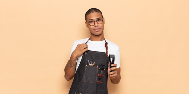 Jeune homme noir à l'air arrogant, réussi, positif et fier, pointant vers lui-même