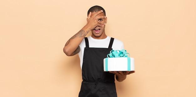 Jeune homme noir à l'air choqué, effrayé ou terrifié, couvrant le visage avec la main et regardant entre les doigts