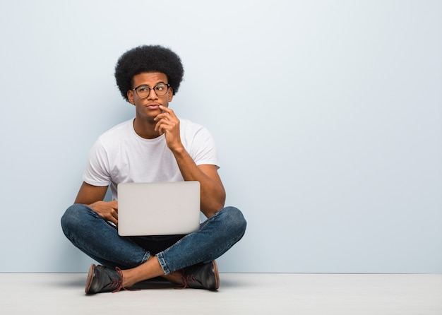Jeune homme noir assis sur le sol avec un ordinateur portable doutant et confus