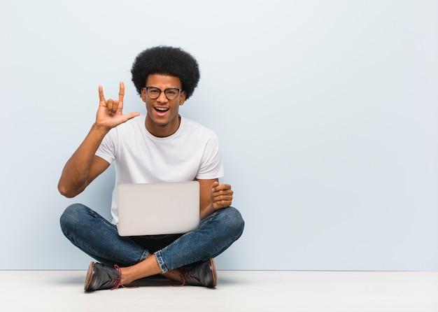 Jeune homme noir assis sur le sol avec un ordinateur portable faisant un geste rock