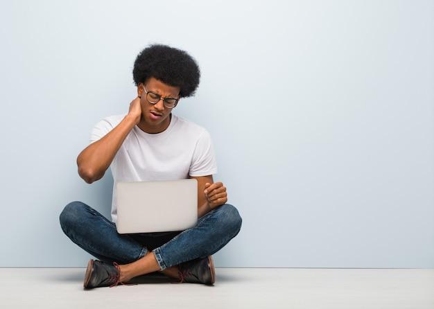 Jeune homme noir assis sur le sol avec un ordinateur portable souffrant de douleurs au cou