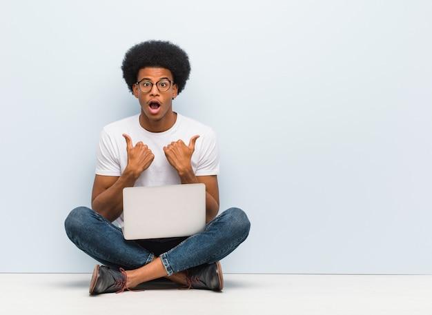 Jeune homme noir assis sur le sol avec un ordinateur portable surpris, sent réussi et prospère