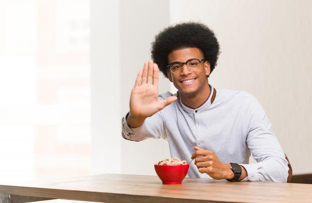 Jeune homme noir ayant un petit-déjeuner mettre la main devant