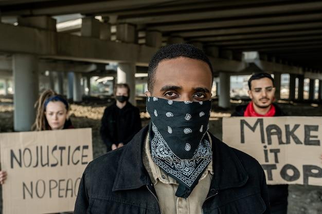 Jeune homme noir en bandana sur le visage debout contre les gens qui protestaient avec des banderoles sous le pont