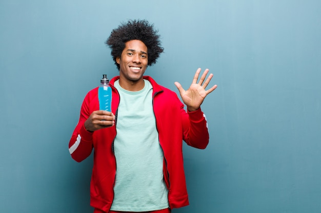 Jeune homme noir avec une boisson sportive contre le mur bleu grunge