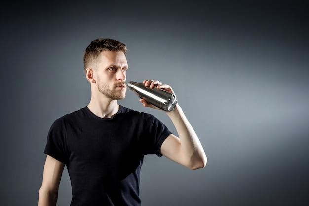 Jeune homme sur le noir boit de l'eau de bouteille de remise en forme