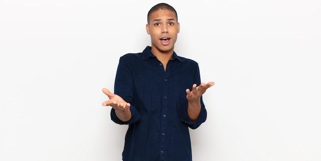 Jeune homme noir bouche bée et étonné, choqué et étonné d'une incroyable surprise