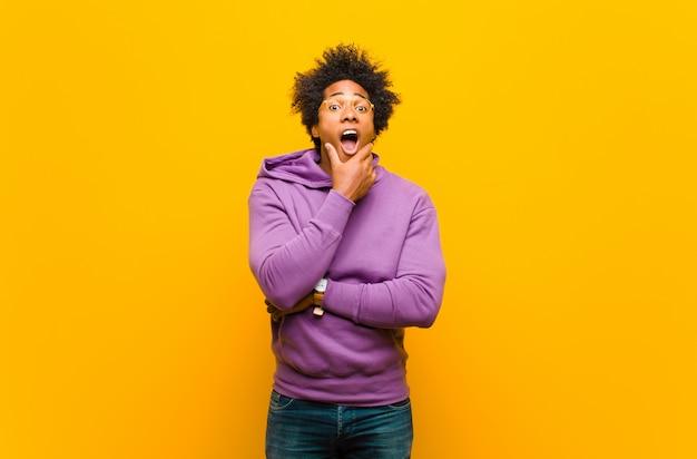 Jeune homme noir avec la bouche et les yeux grands ouverts et la main sur le menton, se sentant désagréablement choqué, disant quoi ou wow contre le mur orange