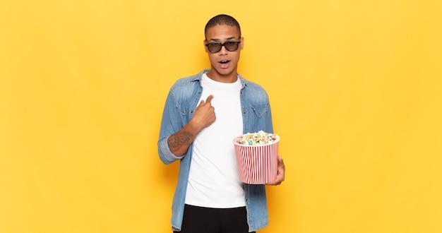 Jeune homme noir à la choqué et surpris avec la bouche grande ouverte, pointant vers soi