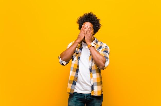 Jeune homme noir couvrant le visage avec les mains, furtivement entre les doigts avec une expression surprise et regardant sur le côté contre le mur orange