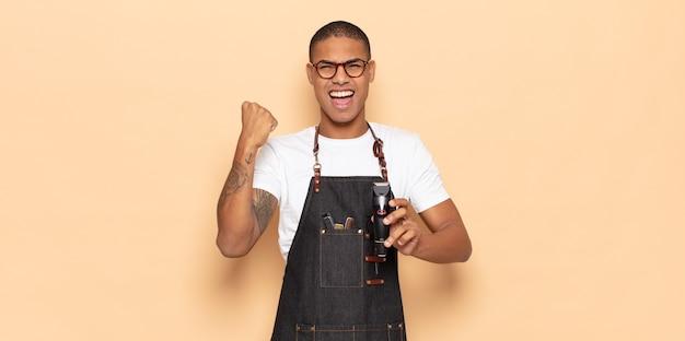 Jeune homme noir criant agressivement avec une expression de colère ou avec les poings serrés célébrant le succès