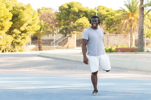 Jeune homme noir dans des écouteurs travaillant dans un parc