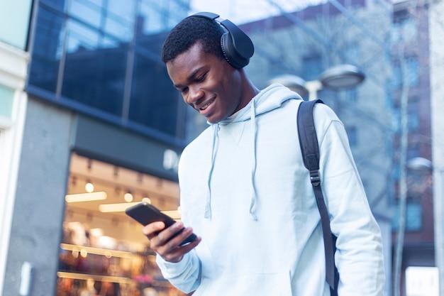 Jeune homme noir debout dans la rue tout en écoutant de la musique au casque