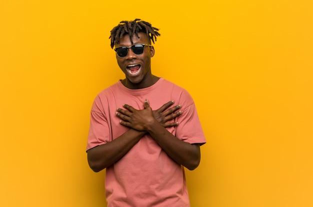 Jeune homme noir décontracté portant des lunettes de soleil en riant en gardant les mains sur le cœur, le concept du bonheur.