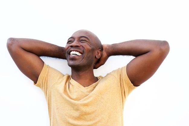 Jeune homme noir détendu contre un mur blanc