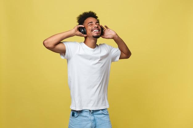 Jeune homme noir, écouter de la musique avec ses écouteurs. isolé sur fond jaune.