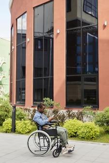 Jeune homme noir handicapé à lunettes communiquant en ligne à l'aide d'un smartphone tout en marchant en fauteuil roulant