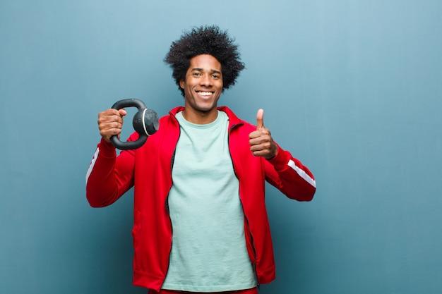 Jeune homme noir homme de sport avec un haltère contre le mur bleu