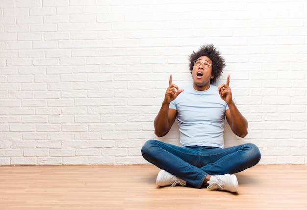 Jeune homme noir, impressionné et bouche ouverte pointant vers le haut avec un regard choqué et surpris assis sur le sol à la maison
