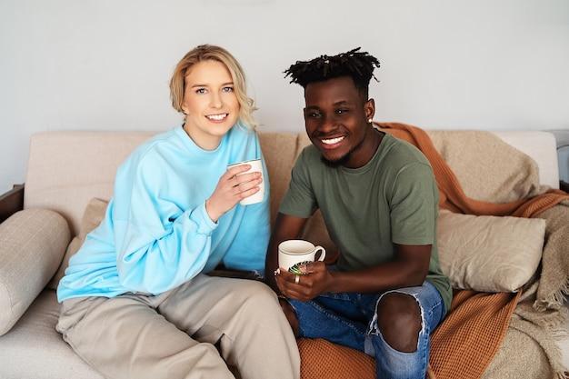 Jeune homme noir et une jeune femme blonde souriante sur le canapé, ils tiennent des tasses blanches dans leurs mains.