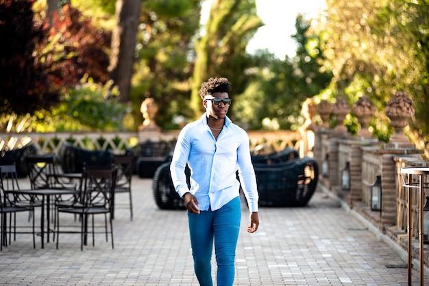 Jeune homme noir avec des lunettes de soleil marchant sur la terrasse d'un bar.