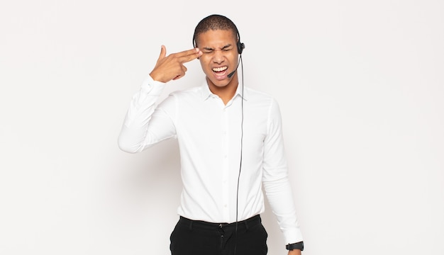 Jeune homme noir à la malheureuse et stressée, geste de suicide faisant signe de pistolet avec la main, pointant vers la tête