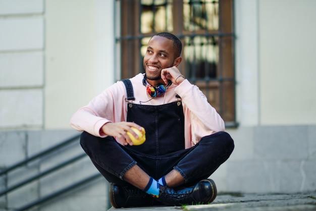 Jeune homme noir mange une pomme assis sur les marches urbaines.