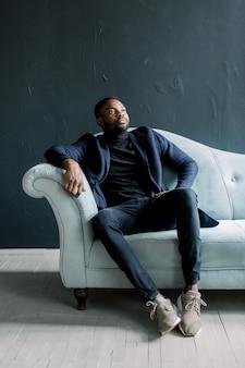 Jeune homme noir en manteau sur fond sombre assis sur un canapé bleu a croisé les doigts. mode portrait de jeune homme en chemise noire en studio