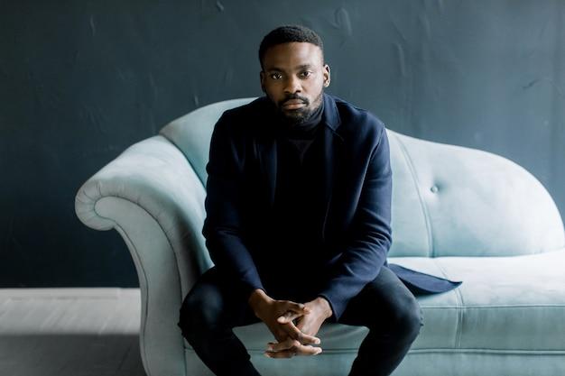 Jeune homme noir en manteau sur fond sombre assis sur un canapé bleu a croisé les doigts