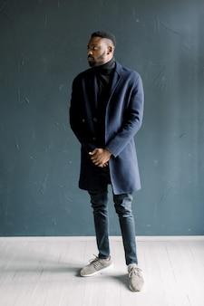 Jeune homme noir en manteau sur fond sombre. studio photo professionnel. mode portrait de jeune homme en chemise noire en studio.