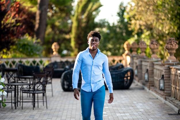 Jeune homme noir marchant sur la terrasse d'un bar.