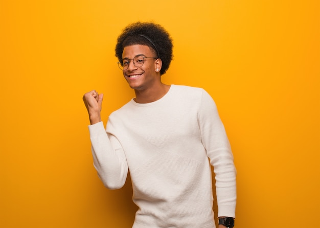 Jeune homme noir sur un mur orange danser et s'amuser