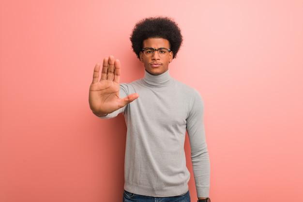 Jeune homme noir sur un mur rose, mettant la main devant
