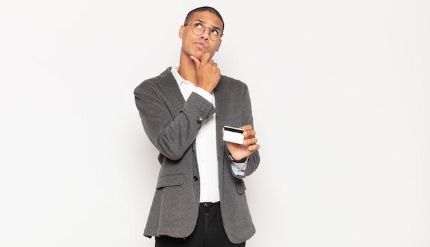 Jeune homme noir pensant, doutant et confus, avec différentes options, se demandant quelle décision prendre