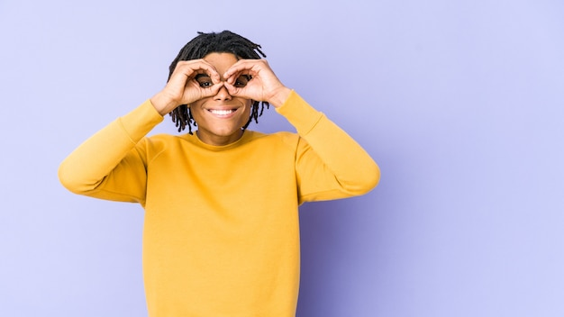 Jeune homme noir portant une coiffure rasta montrant un signe correct sur les yeux
