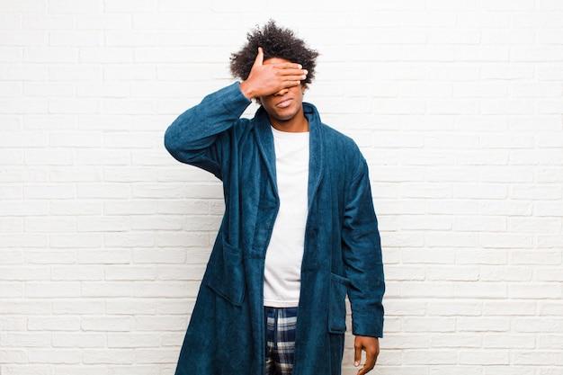 Jeune homme noir portant un pyjama avec une robe couvrant les yeux d'une main, effrayé ou anxieux, se demandant ou aveuglément attendant une surprise contre une brique