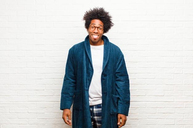 Jeune homme noir portant un pyjama avec une robe dégoutée et irritée, tirant la langue, n'aimant pas quelque chose de méchant et dégueulasse