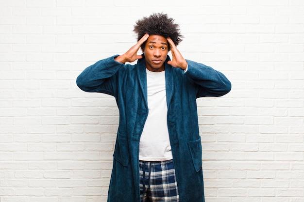 Jeune homme noir portant un pyjama avec une robe à la fois concentrée, réfléchie et inspirée, faisant du brainstorming et imaginant avec les mains sur le front